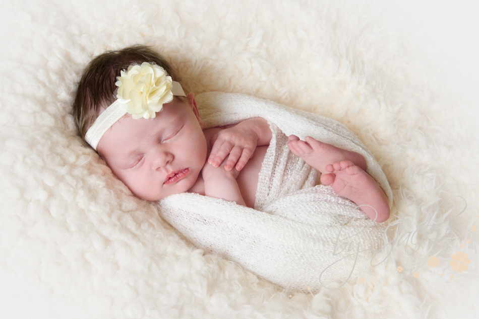 Photo of newborn baby girl asleep on her back wrapped in cream with cream headband near