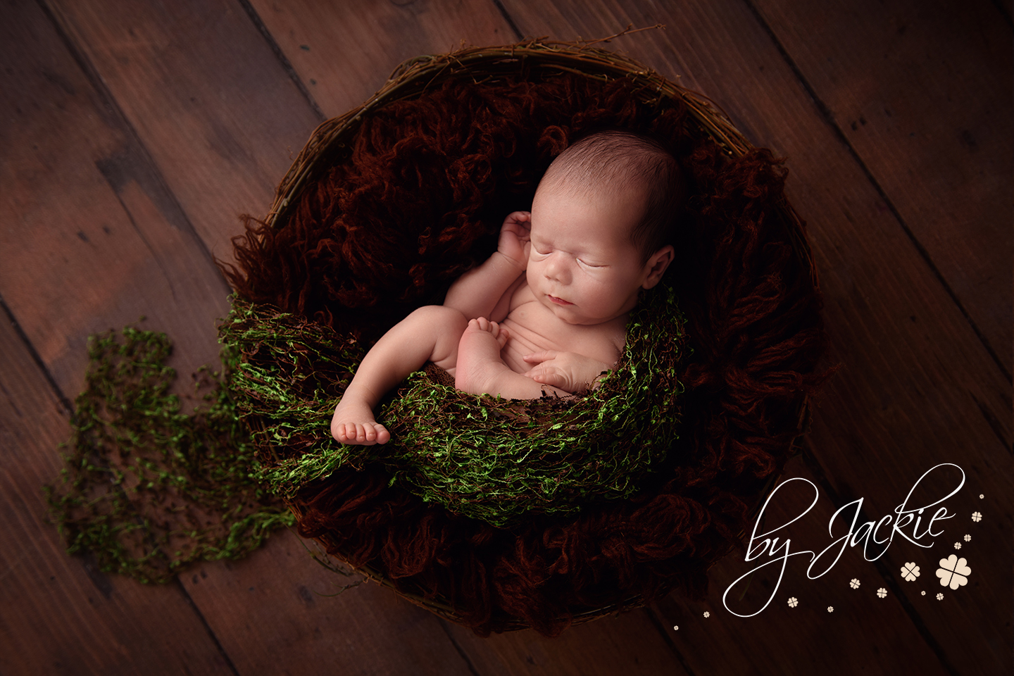 Image of newborn baby boy nestled in asleep by Babies By Jackie. Baby photographer with studio located in Market Weighton, near Pocklington and York, North Yorkshire UK