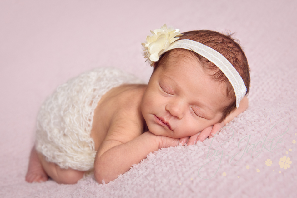 Photo of newborn baby girl wearing headband image copyright by jackie photography hemingbrough between