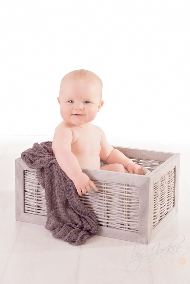 Photo of older baby, sat in a basket. Photo By Jackie Photography in Selby