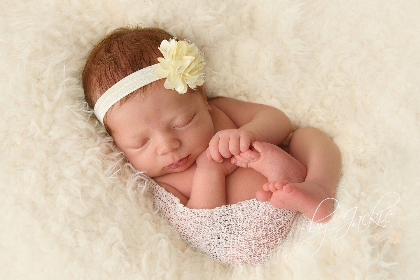 Baby girl asleep in soft cream blanket by Babies By Jackie Photography in Market Weighton near York, North Yorkshire, UK