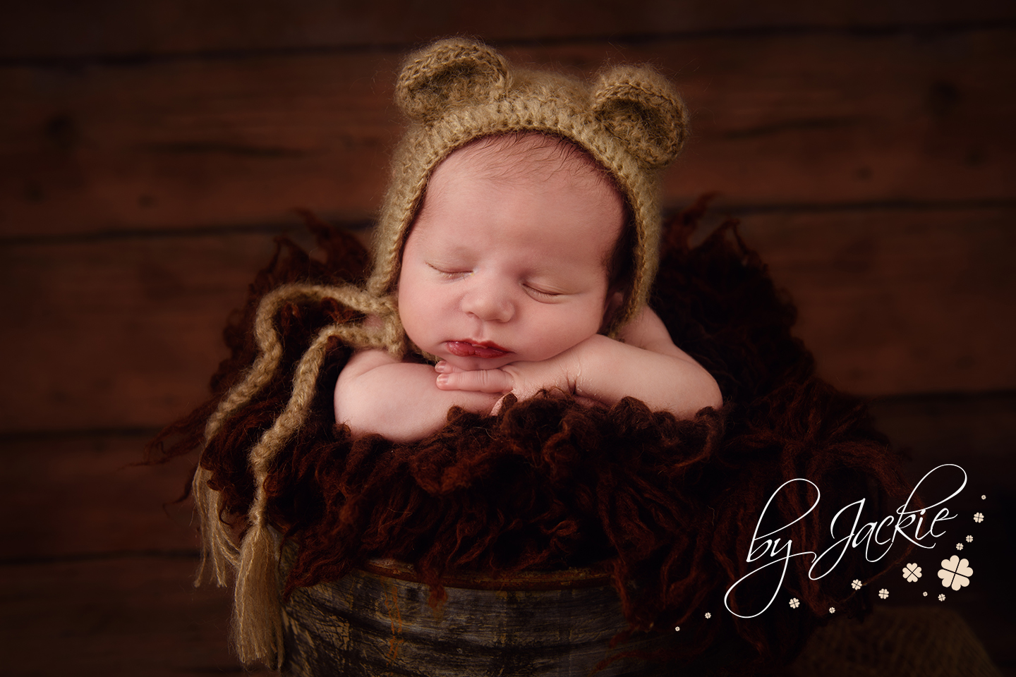 Image of newborn baby boy with teddy bear hat posed in a bucket by Babies By Jackie in North Yorkshire UK