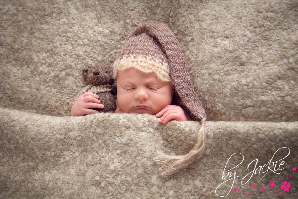 Photograph of a baby boy snuggling his teddy wearing a night cap. Image by Babies By Jackie, specialist baby photographer in Yorkshire, UK