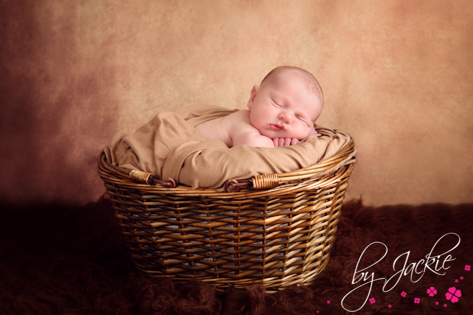 Baby boy asleep in a basket. Image by Babies By Jackie Photography in Yorkshire and East Ridings, UK