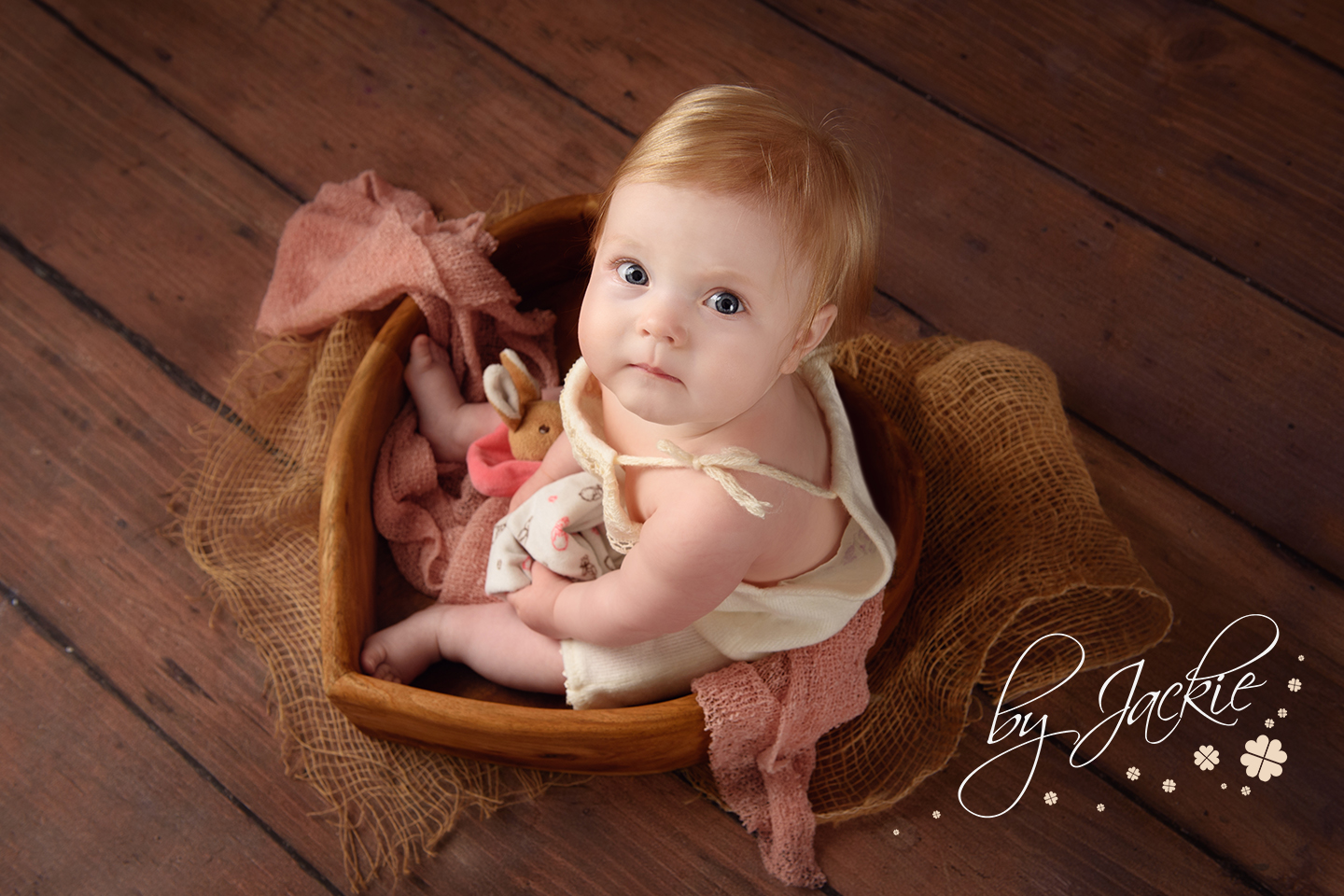 Milestone photography by Babies By Jackie. Image of 8 month old baby girl sitting in heart shaped bowl. Market Weighton, York, Pocklington, Malton, Hessle, Asselby, Beverley, South Cave, Yorkshire UK