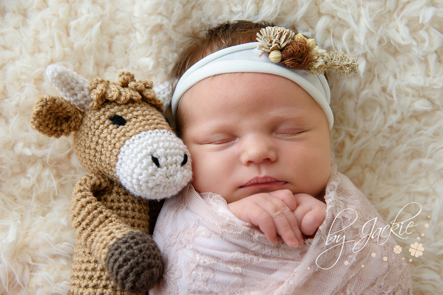 Baby girl cuddled up with her keepsake hand made cow from Babies By Jackie in Yorkshire, UK